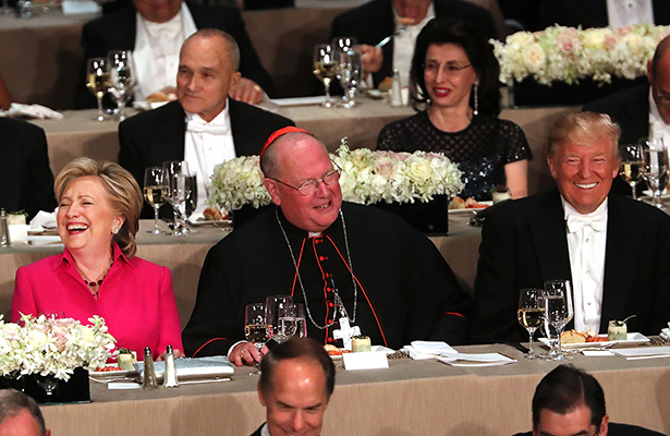 NEW YORK, NY - OCTOBER 20: Sitting between Cardinal Timothy Dolan, Hillary Clinton and Donald Trump attend the annual Alfred E. Smith Memorial Foundation Dinner at the Waldorf Astoria on October 20, 2016 in New York City.The white-tie dinner, which benefits Catholic charities and celebrates former Governor of New York Al Smith, has been attended by presidential candidates since 1960 and gives the candidates an opportunity to poke fun at themselves and each other.   Spencer Platt/Getty Images/AFP